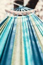 Empty Textile Hammock In Perspective With Shallow Depth Of Field Close Up. Striped Blue Hammock Hanging Tied To Tree First Person View.