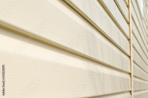 Tablou Canvas Light beige vinyl siding of the house. Plastic panels texture.