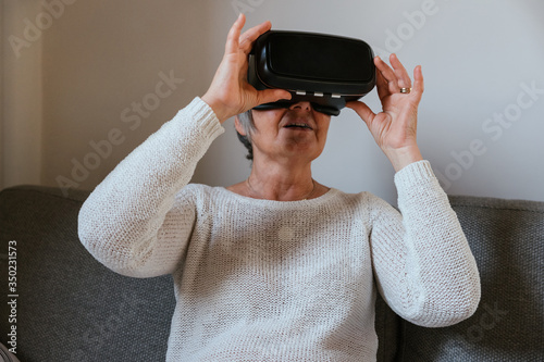 Fotografie, Obraz Adult woman at home on sofa having fun with vr glasses for advanced realty heads