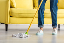 Cropped View Of Woman Mopping Floor With Mop In Living Room