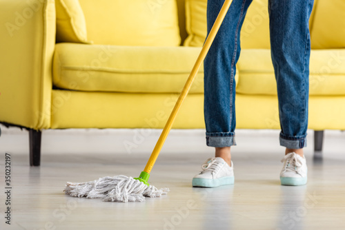 Fotografia Cropped view of woman mopping floor with mop in living room