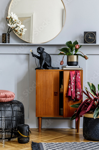 Modern concept of home staging with design wooden commode, round mirror, shelf, clock, plant, rattan pouf, carpet, books and elegant personal accessories at stylish living room.
