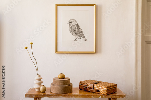 Obraz Stylish concept at living room interior with gold mock up frame, wooden bench, boxes, dried flowers in vase, white wall and elegant personal accessories in modern home decor. - fototapety do salonu