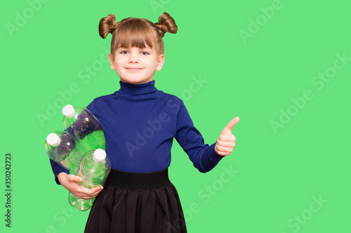 Positive little ecologist girl holding trash bag with plastic bottles and show t Canvas Print