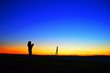 canvas print picture - Silhouette Woman With Camera Standing On Field Against Clear Blue Sky