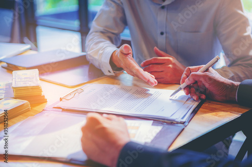 Fototapeta Businessman puts signature on contract at business meeting and passing money after negotiations with business partners. Selected focus obraz
