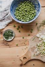 Bol De Petits Pois Crus Et Herbes, Sur Une Table En Bois