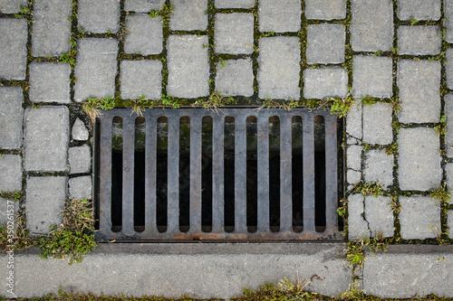 iron culvert on cobblestone street Fototapeta