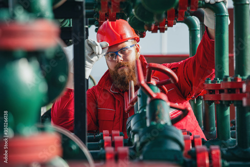 Obraz Oil and Gas Industry Worker. Engineer working on pipeline equipment for oil and gas company. - fototapety do salonu