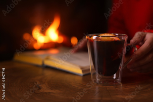 Fototapeta Woman with mulled wine reading book near fireplace indoors, closeup