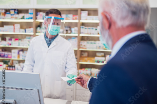 Professional pharmacist with protective mask and face shield on his face  working with customer in modern drugstore.