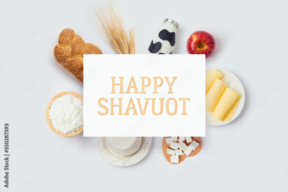 Fototapeta Jewish holiday Shavuot banner design with milk bottle, cheese and bread on white background. Top view from above