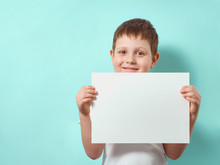 Four-year-old Boy Smiles And Holds Blank White Paper Sheet. Happy Child On Blue Background With Copy Space For Message, Mock Up