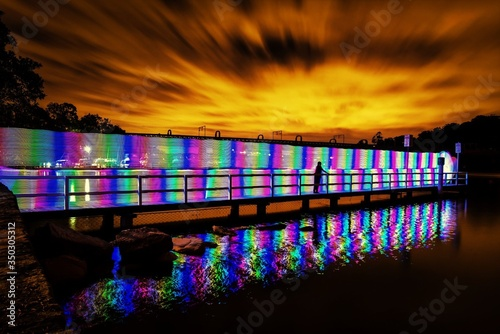 Obraz na plátne Silhouette Person Standing On Illuminated Colorful Footbridge Against Sunset Sky