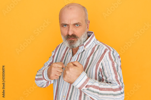 Photo Isolated image of healthy strong bald male pensioner wearing striped shirt keeping fists clenched standing in defensive position, ready to punch enemy, looking with animosity