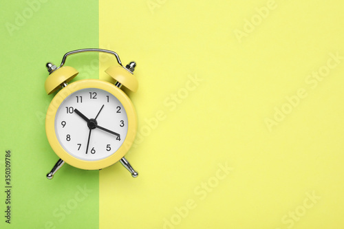 Top view of alarm clock on color background, space for text Canvas