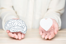 Female Hands Holding Paper Cut Brain And Soul. Conflict Between Emotions And Rational Thinking. Balance And Equilibrium Between Mind And Heart Concept