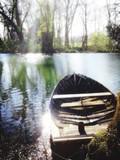 Fototapeta Na sufit - Moored Boat In Calm Lake Against Trees