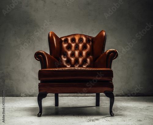 Fototapeta Luxorious brown leather vintage armchair standing in a dark studio obraz
