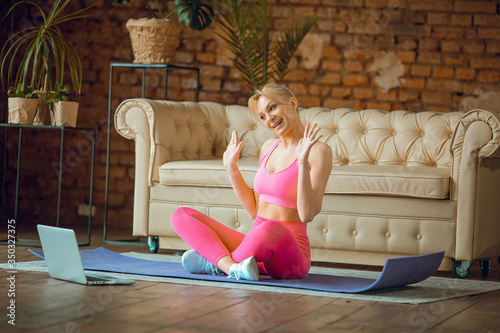 Fototapeta young fit blogger girl seating on  yoga  mat in sport outfit with laptop doing online  workout at home, recording online aerobic tutorials from home, exercise on camera obraz na płótnie
