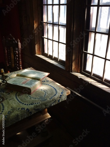 Fotografiet Holy Book On Table By Window