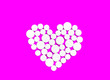 Leinwandbild Motiv White medicine pills in the shape of a heart on a pink background top view with copy space.