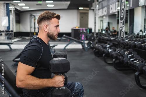 Photo hombre joven atractivo barbudo entrenando en gimnasio moderno