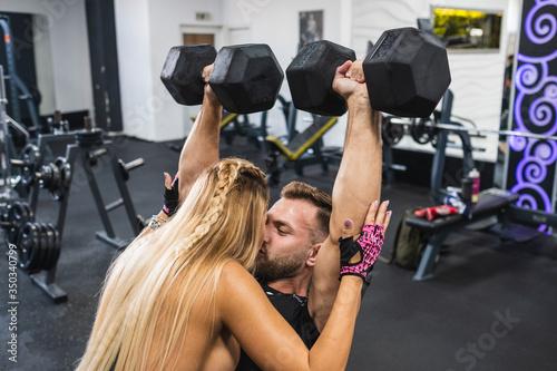 pareja joven dándose un beso durante entrenamiento en gimnasio Canvas Print