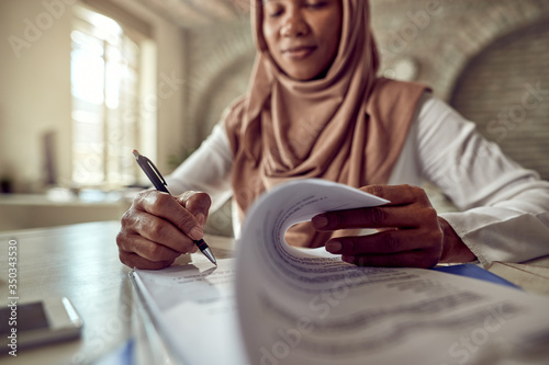 Fototapeta Close-up of Muslim businesswoman signing documents in the office. obraz