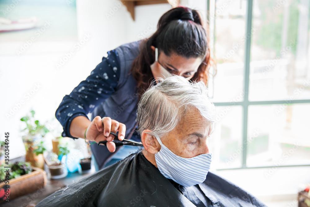 Fototapeta Senior woman getting a haircut at home during Covid-19 pandemic wearing face mask