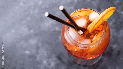 Leinwand Poster Classic italian aperitif aperol spritz cocktail in glass with ice cubes and with