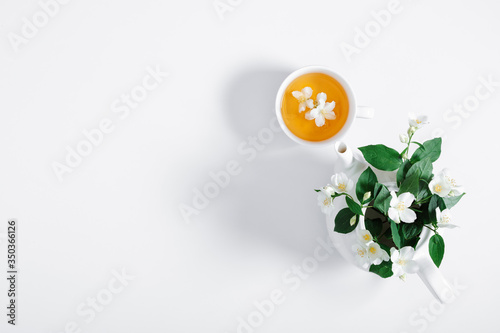 Jasmine flowers and teapot on white background Canvas Print