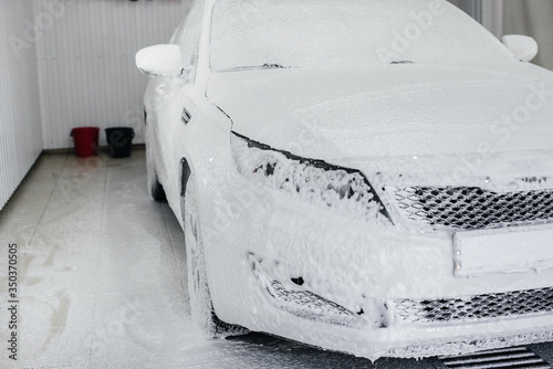 Fototapety, obrazy: Modern washing with foam and high-pressure water of a white car. Car wash