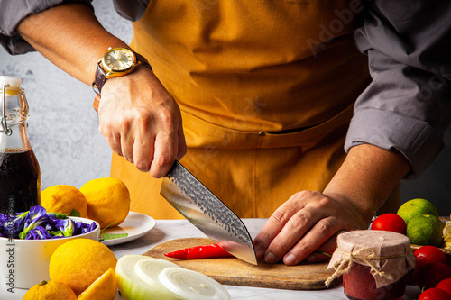 Fotografiet Male slicing chilli pepper on wooden cutting board by Japanese kitchen damaskus