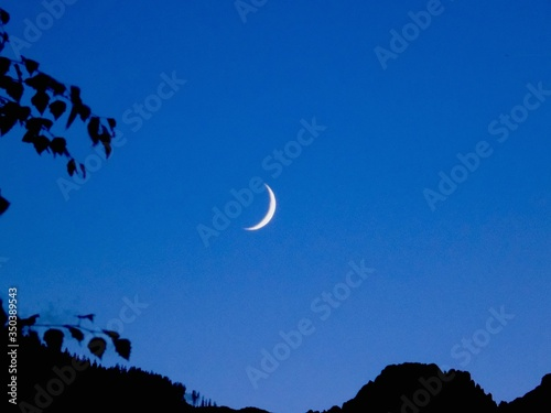 Fotografie, Obraz Low Angle View Of Crescent Moon Against Blue Sky