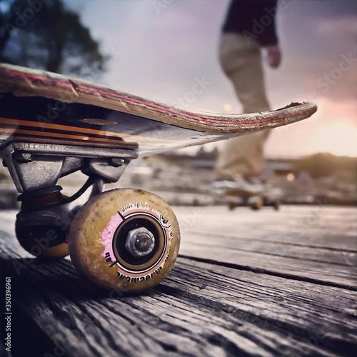 Fototapeta Close-up Of Skateboard With Blurred Man Skateboarding Behind obraz