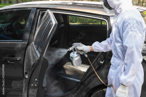 Fototapeta Close up hand of specialist cleaner wearing personal protective equipment PPE using chemical alcohol spray cleaning inside car to disinfect and decontaminate coronavirus covid-19 obraz