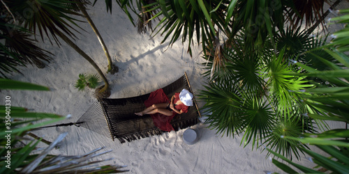 Photo Woman rests in loose red summer dress and hat hanging in hammock surrounded by p