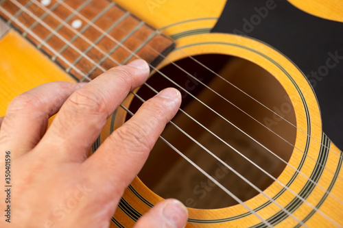 A top down view of a hand strumming the strings of an acoustic guitar Slika na platnu