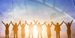 Silhouette of happy business teamwork making high hands over head in sunset sky background for business teamwork concept