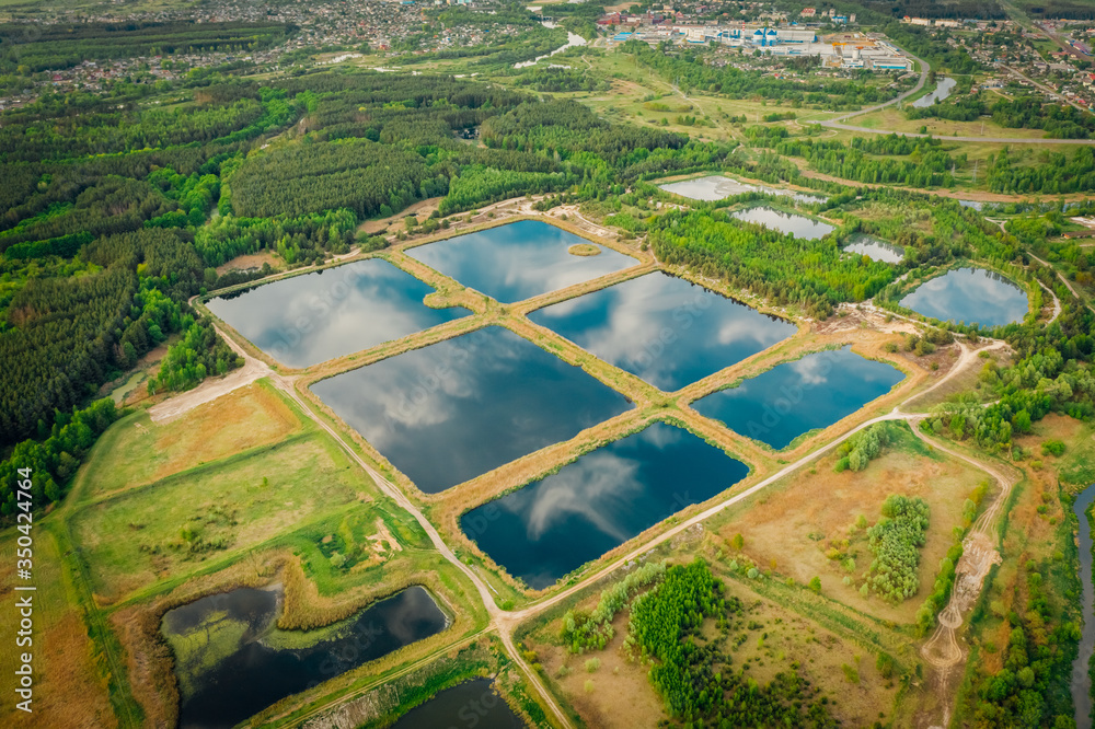 Fototapeta Artificial pond, for maintenance and purification of water from sewage. Water storage for purification from impurities. Urban water treatment in clusters. Reflections sky in mirror water. Aerial view