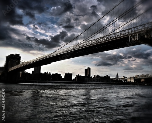 Fotografering Manhattan Bridge Over East River Against Cloudy Sky In City