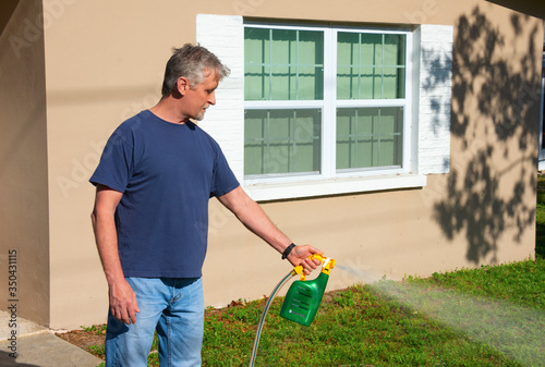 Homeowner man spraying weed killer on the grass on grass in his yard with hose a Canvas Print