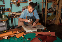 Leather Craftsman Working With Natural Leather Using Hammer. Handbag Master At Work In Local Workshop. Handmade Concept