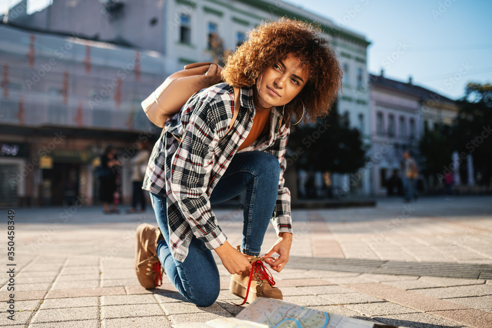 Fototapeta Young attractive female tourist with curly hair crouching at square and tying shoelace.