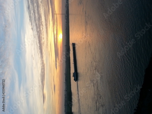Fotografiet Barge Sailing On Sea Against Sky At Sunset