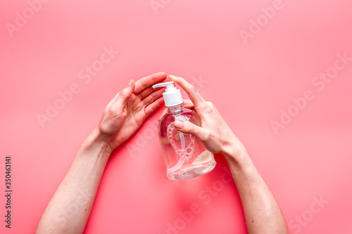 Fototapeta Disinfecting hands. Dispensing sanitizer on pink background top view obraz