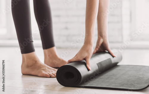 Fototapeta Female hands rolling up exercise mat and preparing doing yoga. Young woman meditating at home. Girl practicing yoga in class. Relaxation, body care, healthy lifestyle, exercising, training concept obraz