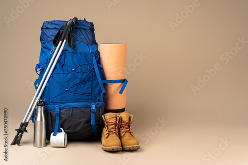 Obraz Blue backpack and hiking boots. Mountain gear ready for trip close up - fototapety do salonu