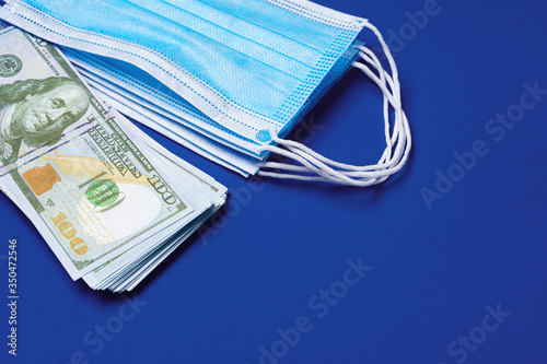 Close up of medical protective masks and american dollar banknotes on blue background. Shortage of masks and rise in price concept